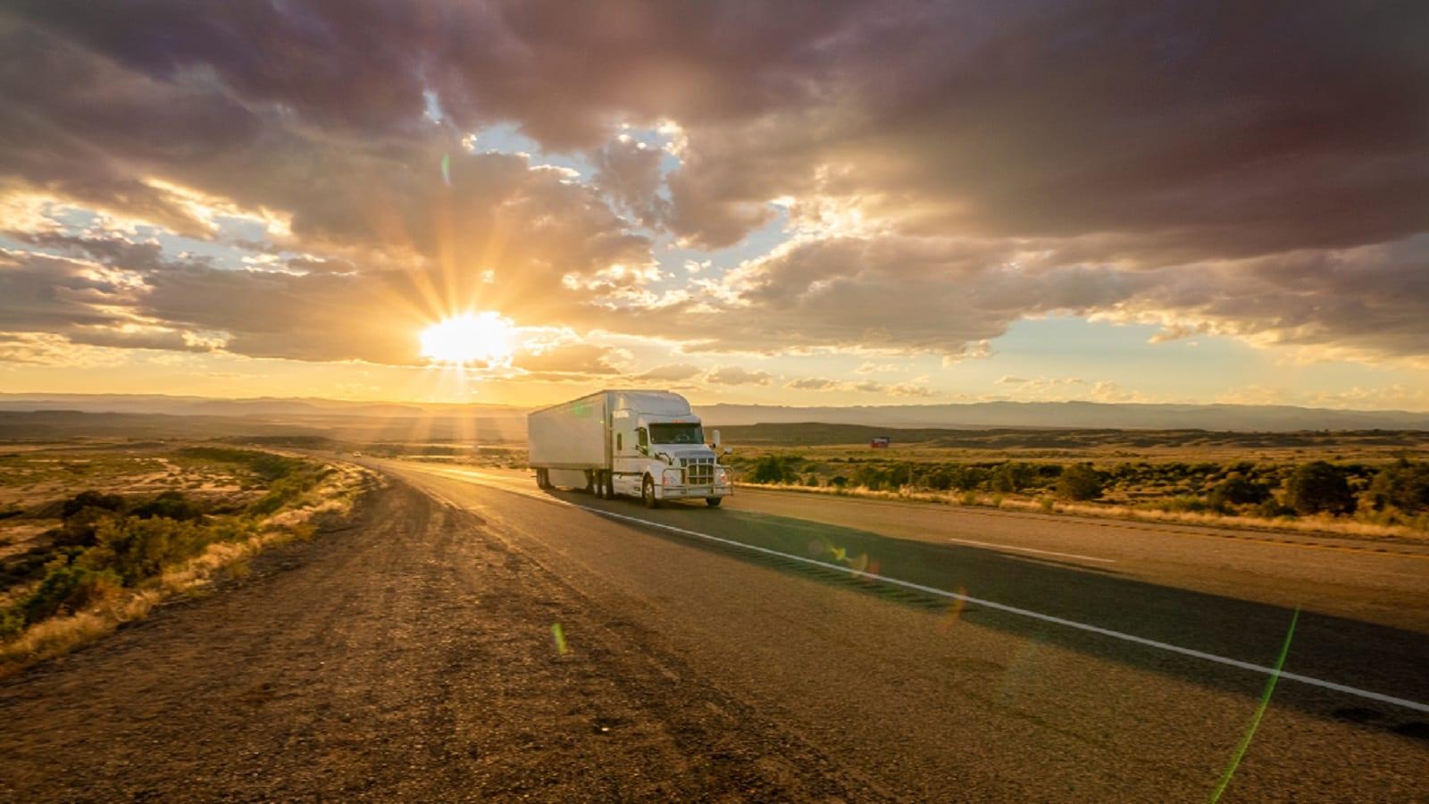Semi-Truck Driving At Dusk Stock Photo