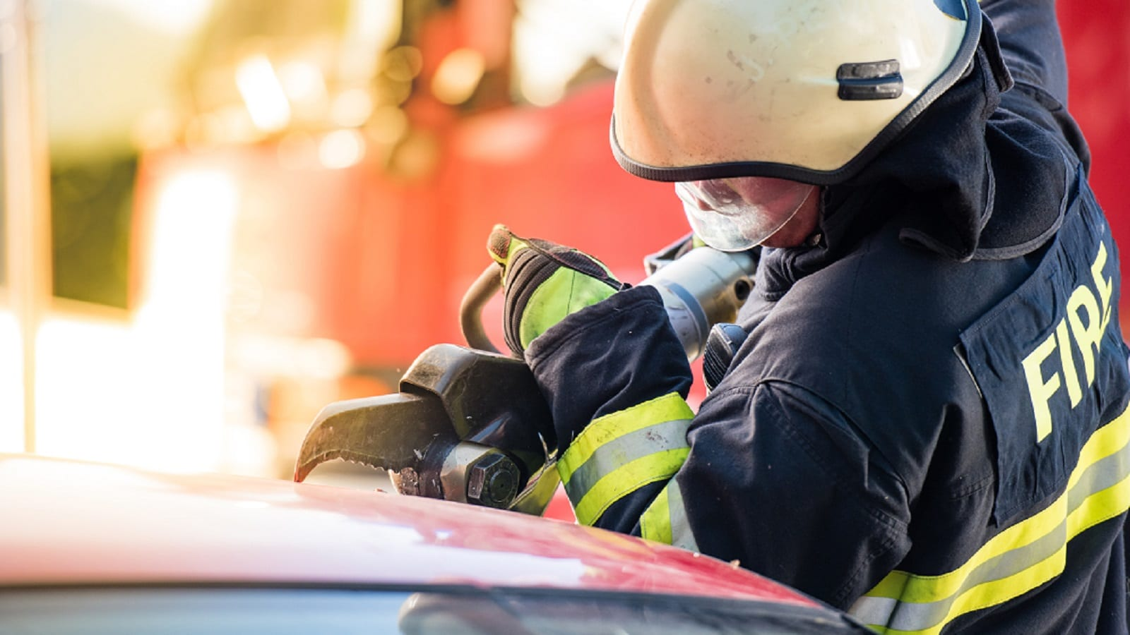 Firefighter Using Jaws of Life During Auto Accident Stock Photo