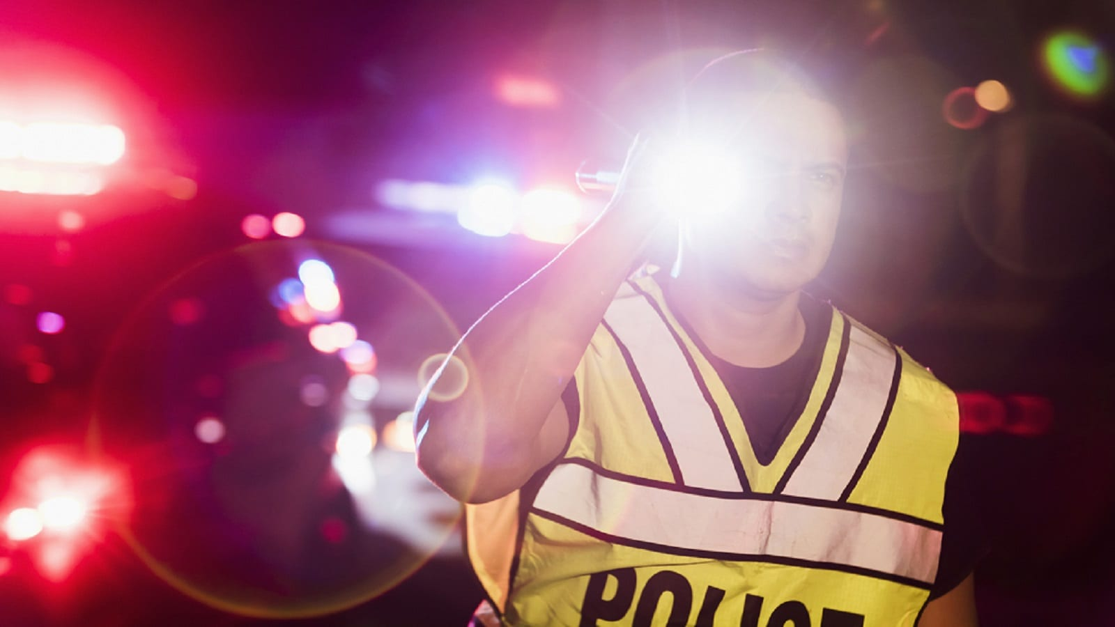 Police Officer Shining Flashlight Stock Photo