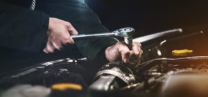 auto mechanic working on car engine