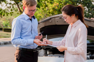 Insurance agent writing document on clipboard examining car after accident, Insurance concept